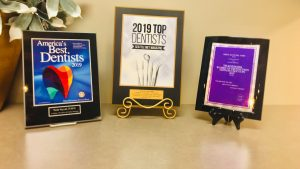 Dr. Neda Sayyah's top dentist and best dentist accolades displayed on a desk